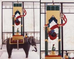 Horloge à eau d'AI Jazari. Un cornac est assis sur le cou de l'éléphant et tient en sa main gauche un pieu pointu et sa droite brandit un marteau. L'éléphant porte sur son dos une plate-forme quadrangulaire avec un baldaquin surmonté d'une tour, au sommet de laquelle perche un oiseau. Sur le haut de la coupole, 15 ouvertures sont alignées. Elles ont la taille d'un Dirham moyen. Elles sont couvertes à l'intérieur par un anneau d'argent moitié noir, moitié blanc. Reproduction contemporaine, collection du Musée d'horlogerie du Locle, Suisse. Photo G. Savini, Le Locle