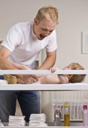 un père change son bébé